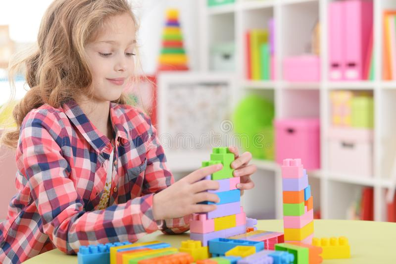 Portrait of little girl playing with colorful plastic blocks at home stock image