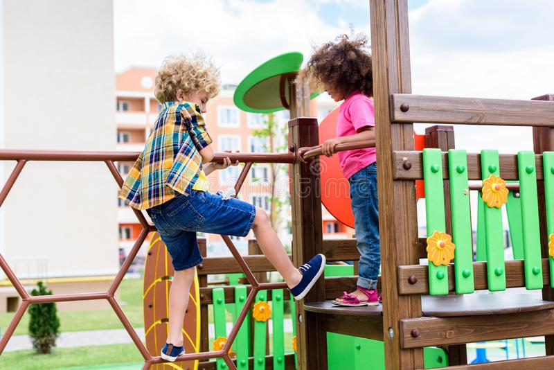 Curly multiethnic little children climbing and having fun. At playground stock image