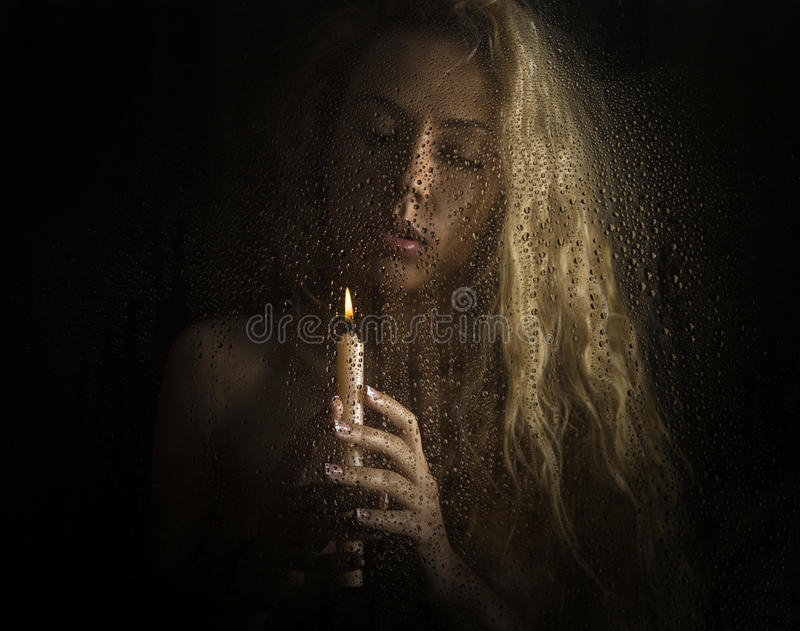 Curly nude blonde woman with candle on dark background stock photos