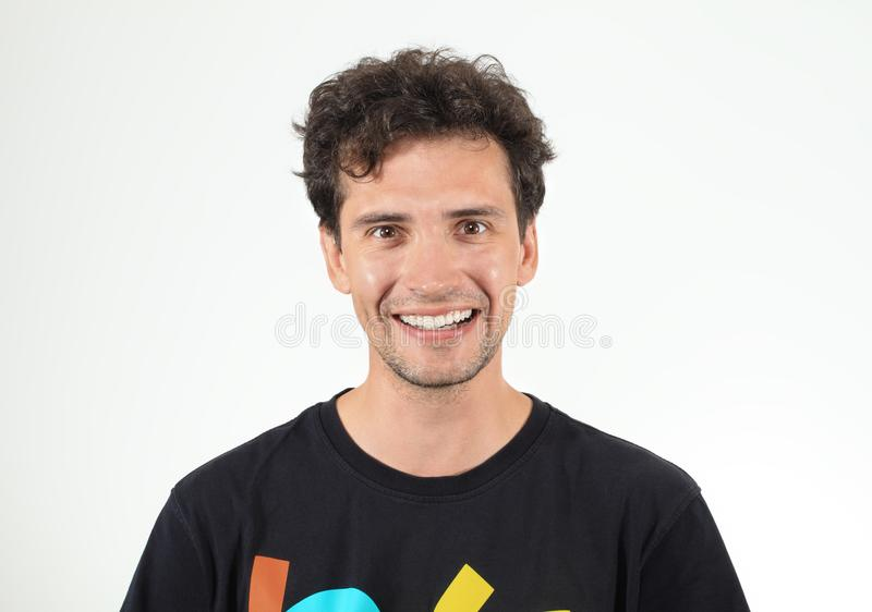 Curly pleased man in black t-shirt smiling stock photo