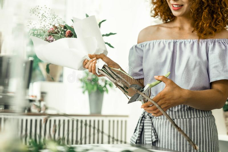 Curly red-haired florist with bright lips finishing beautiful nice bouquet royalty free stock photography