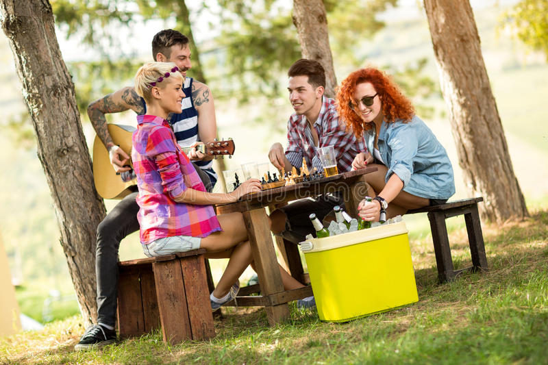 Curly red-haired girl takes out cold beer from picnic handheld r. Efrigerator at summer camp in nature royalty free stock photo