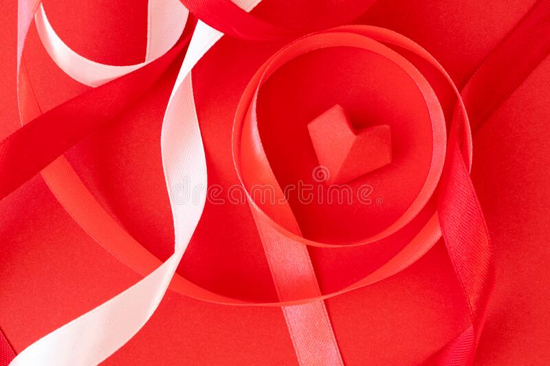 Curly satin ribbons and origami heart on red paper background, close-up. Valentine`s day card, poster. Or invite stock image