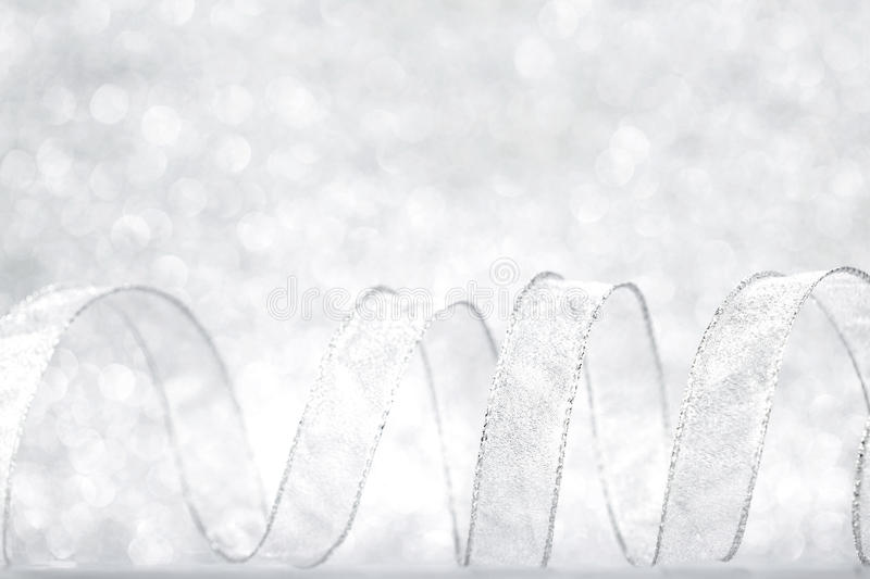 Curly serpentine. Curly silver serpentine on shiny glitter background, holiday concept stock photos