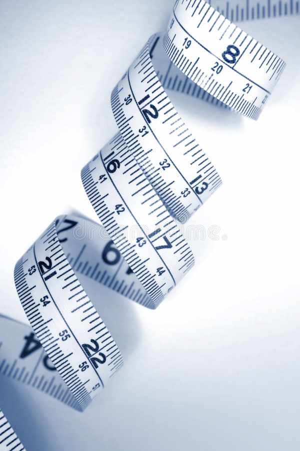 Curly tape measure in inches. A curly tape measure, marked in inches. Good concept for fashion, diet, and weightloss royalty free stock images