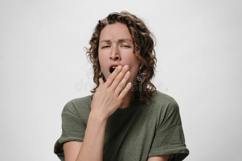 Curly tired sleepy woman yawns and covers mouth with palm, looking bored stock image