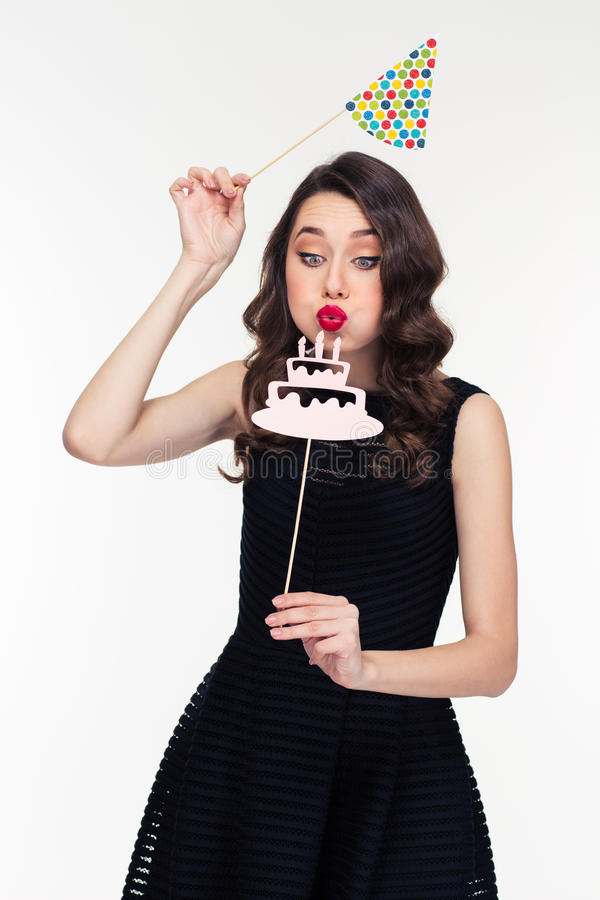 Curly woman blowing on fake birthday cake with candles props. Cute lovely curly retro styled young woman in black dress blowing on fake birthday cake with royalty free stock photo