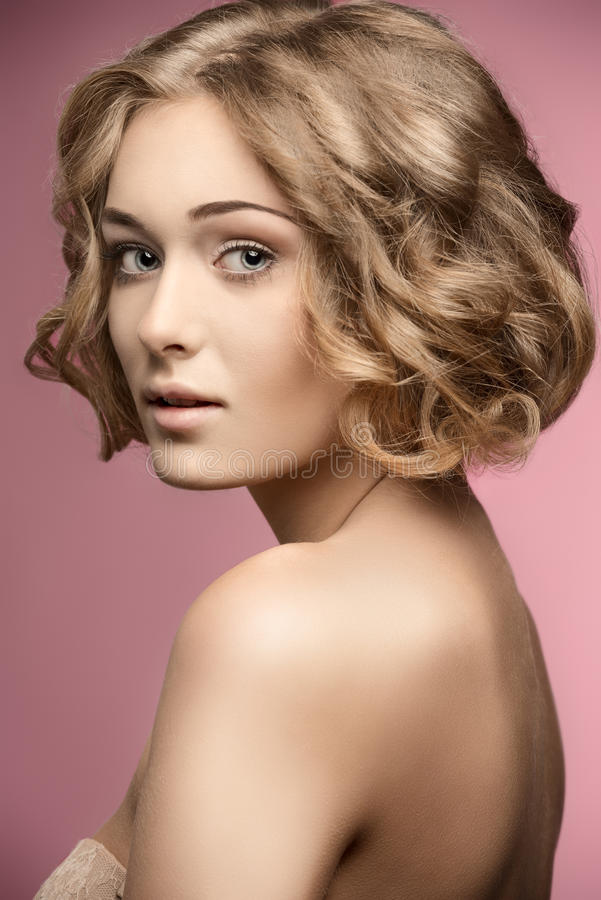 Curly woman with bob hair-cut. Beautiful blonde woman posing with curly bob hair-cut and natural make-up. Naked shoulders, perfect skin stock photography