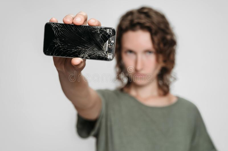 Curly woman need to repair her broken smartphone afteraccident. Isolated on graybackground royalty free stock photos