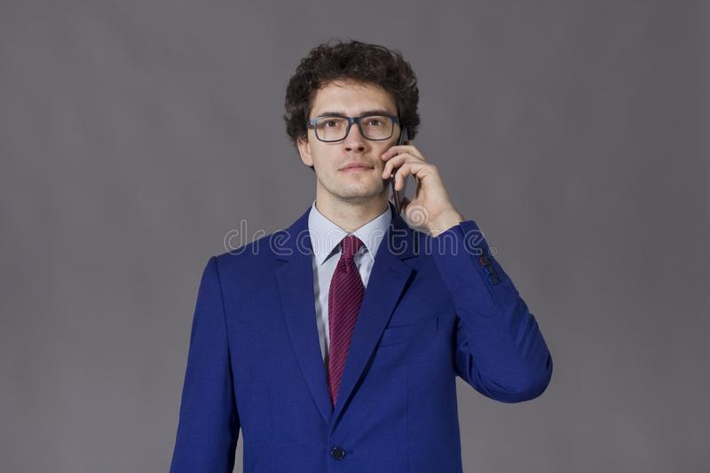 Curly young man with glasses standing with phone stock photos
