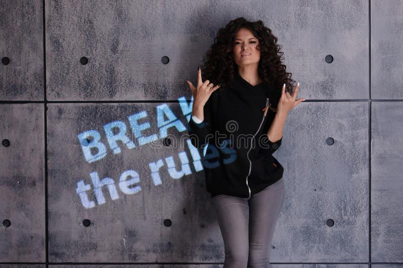 Curly young woman in a strong, boxing pose against a concrete wall background. Colored light sign Break the rules. Portrait of a determined curly young woman in royalty free stock photo