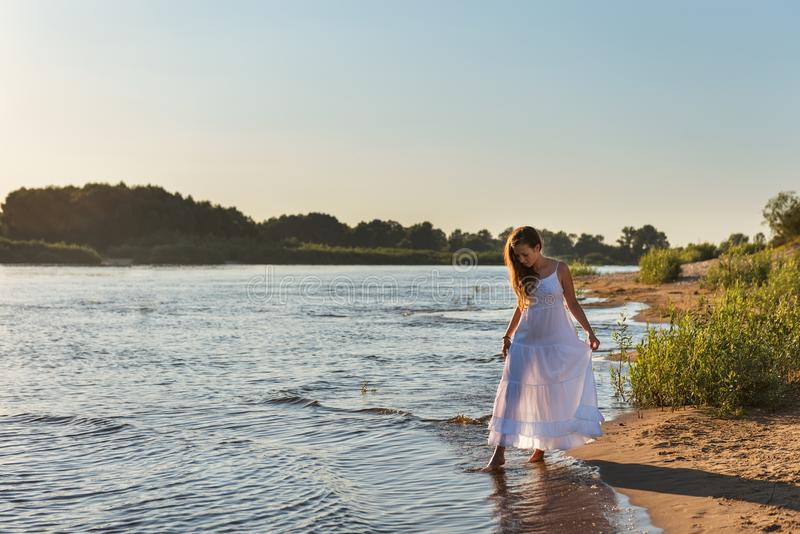 Curly young woman touching the toes of the river water in a white dress in the backlight of the sunrise shining her slender legs stock photography