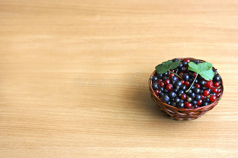 Currants in a wicker basket. Berry background. Black berries and red currants are in a brown wicker basket on old wooden surface royalty free stock photos
