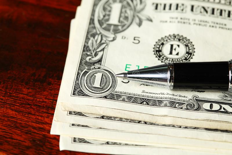 Banknote and ballpen. The currency banknote and chrome ballpen represent the business finance concept related idea royalty free stock images