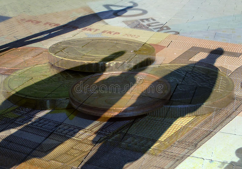 Currency concept. Conceptual image showing people shadows overlaid over European currency royalty free stock images