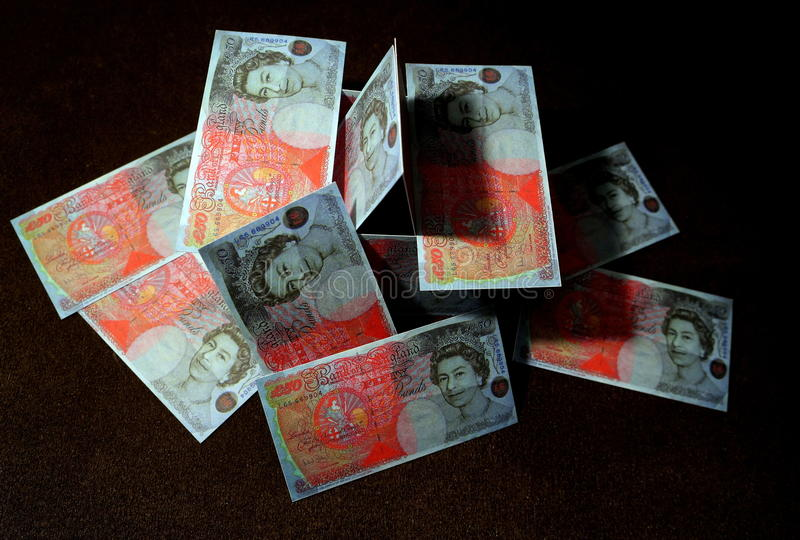 Currency crash. Sterling fifty-pound notes depicted as a house of cards collapsing, signifying various currency crises royalty free stock images