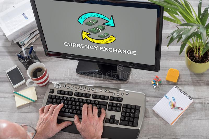 Currency exchange concept on a computer. Man using a computer with currency exchange concept on the screen royalty free stock photography