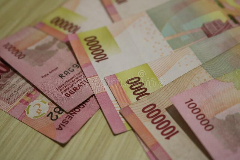 Currency from Indonesia. With each worth of 100,000 rupiah placed on a wooden table royalty free stock photos