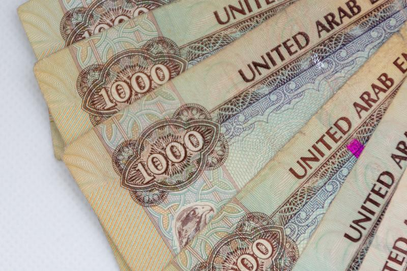 The Currency of the United Arab Emirates UAE - Thousand Dirham notes spread out on a white background. Money exchange. In thousands stock photo