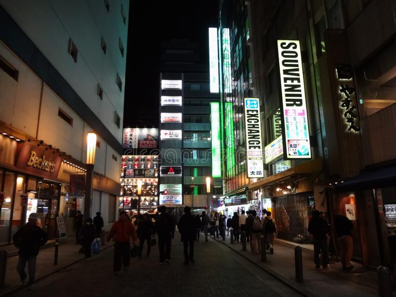 Curreny exchange sign in Akihabara. Akihabara electric town at night, currency exchange and souvenir sign, store fronts, crowded; December 2014 royalty free stock image