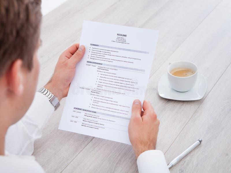 Curriculum vitae de la lectura del hombre de negocios con la taza de té en el escritorio foto de archivo libre de regalías