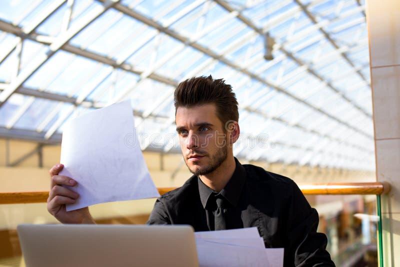 Curriculum vitae masculino de la lectura de la dirección durante día del trabajo en compañía, usando usos del netbook imagen de archivo