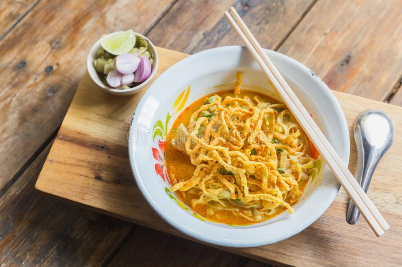 Curried noodle soup Khao soi with chicken meat and spicy coconut milk on wood table. Thai food cuisine northern style. stock images