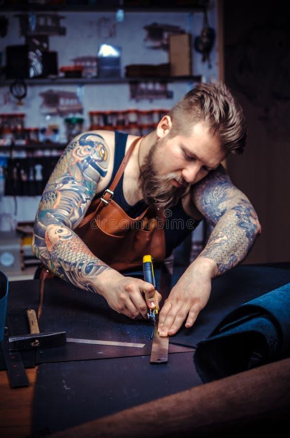 Currier do funcionamento de couro em um produto de couro novo na loja do curtidor fotos de stock