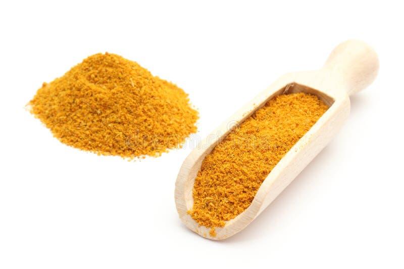 Curry arancio sul cucchiaio di legno. Isolato su fondo bianco immagine stock libera da diritti