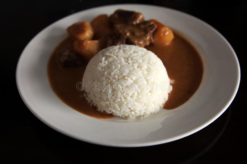 Curry beef with rice. And sauce on a plate royalty free stock image