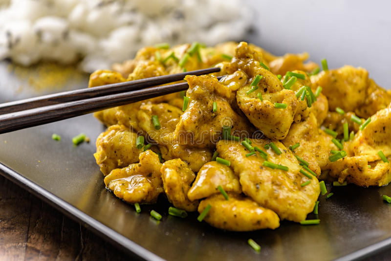Curry chicken and oriental rice in a dish. Curry chicken and oriental rice in a blak dish royalty free stock photo