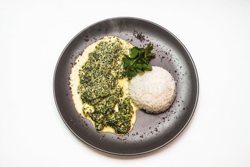 curry del pollo con i verdi e riso su una banda nera immagini stock