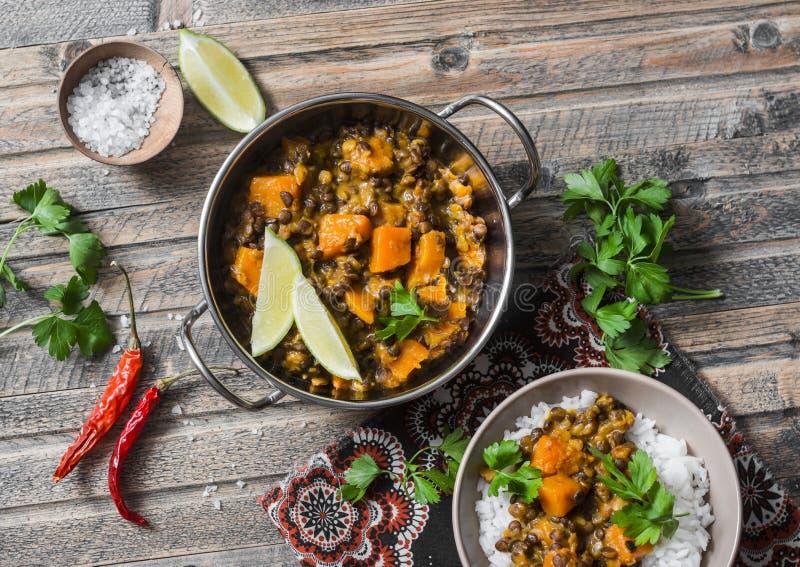 Curry della lenticchia della zucca e riso su una tavola di legno, vista superiore Alimento vegetariano indiano immagine stock libera da diritti