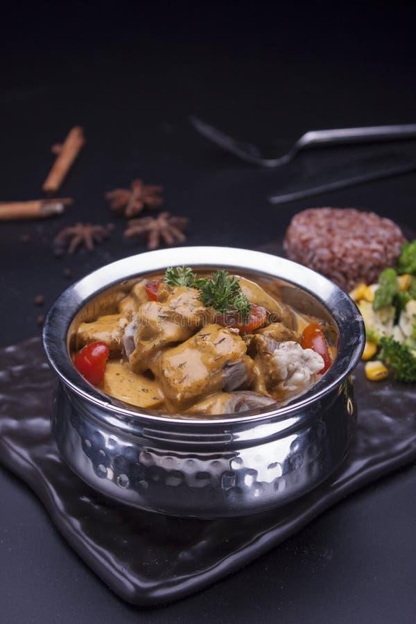Curry indio de la cabra en una mano imagenes de archivo