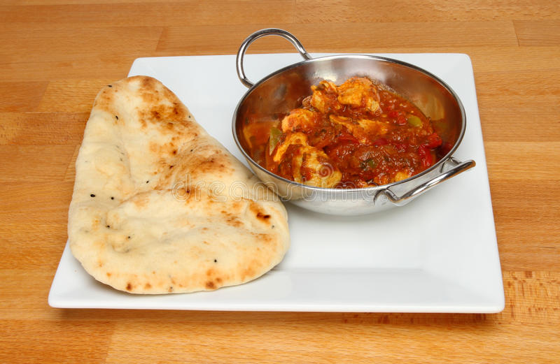 Curry and naan. Chicken curry with a naan bread on a plate upon a wooden table stock images