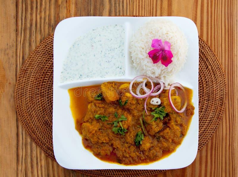 Curry och rice på trätabellen med den rosa blomman royaltyfri foto