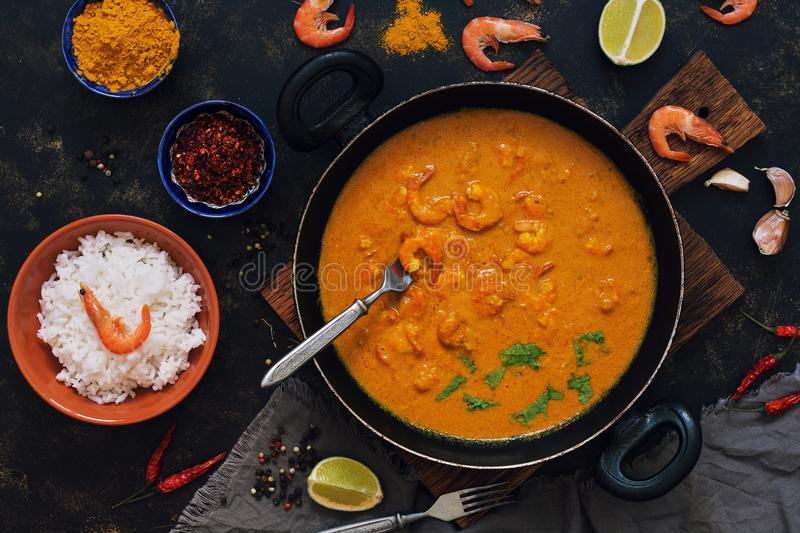 Curry sauce with shrimps in a frying pan. Rice in a bowl, spices, lime.Thai, Indian food. View from above. stock photography