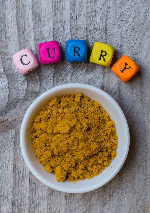 Curry w pucharze z listowym sześcianem na drewnianym tle obrazy stock