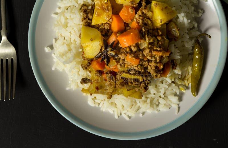 Curry y arroz en la placa, foto de la visión superior en la tabla rústica negra imagen de archivo