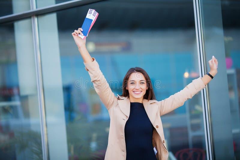 Curso Bilhete de ar da terra arrendada dois da mulher no exterior no passaporte perto do aeroporto foto de stock