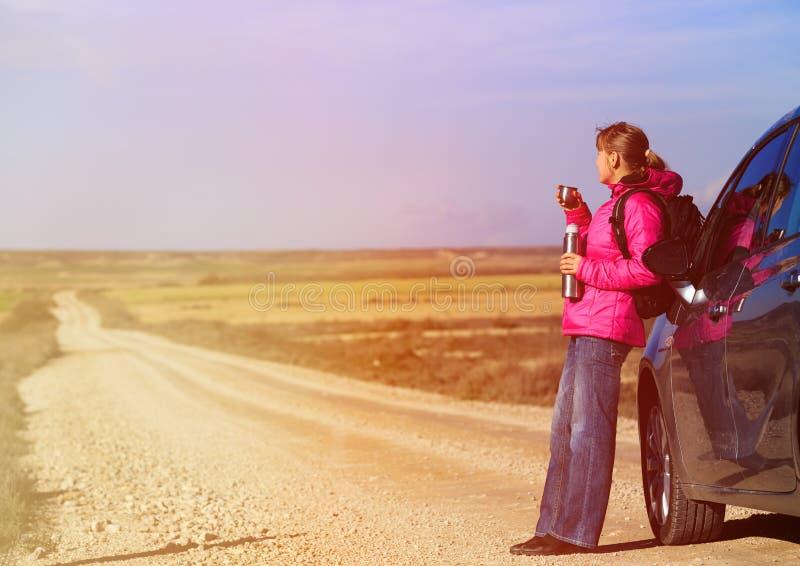 Curso da jovem mulher pelo carro na estrada cênico no inverno imagens de stock royalty free