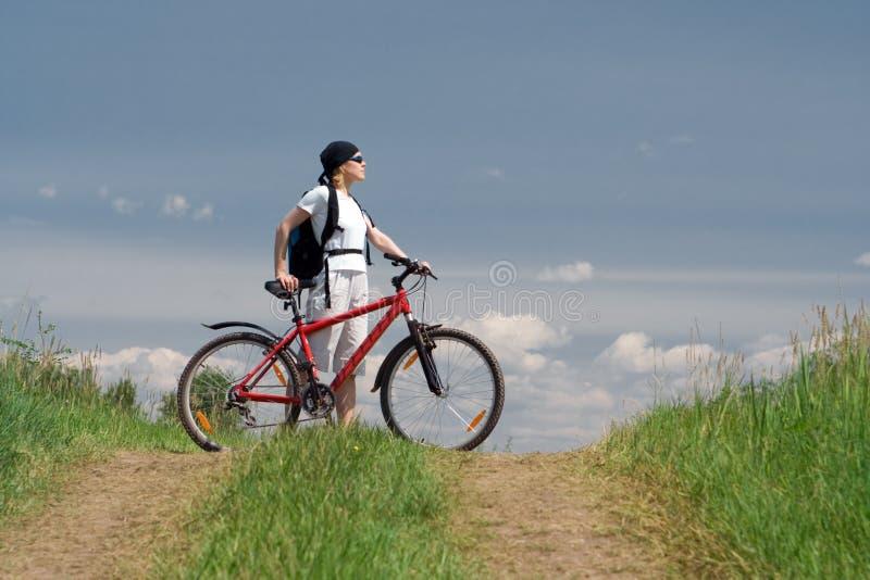 Curso da mulher com bicicleta foto de stock