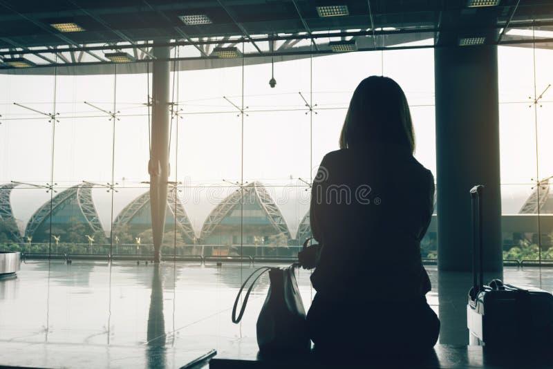 Curso da mulher da silhueta com a bagagem que senta-se no terminal de aeroporto internacional fotografia de stock royalty free