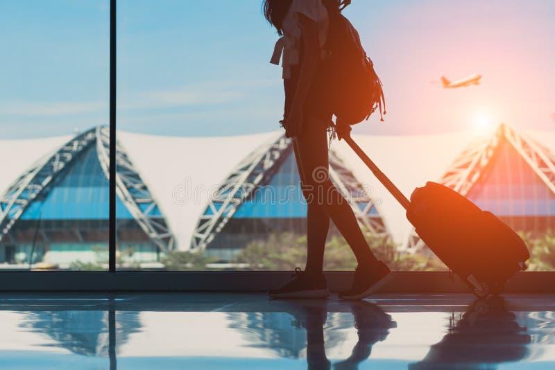 Curso da mulher da silhueta com a janela lateral de passeio da bagagem no international do terminal de aeroporto imagens de stock