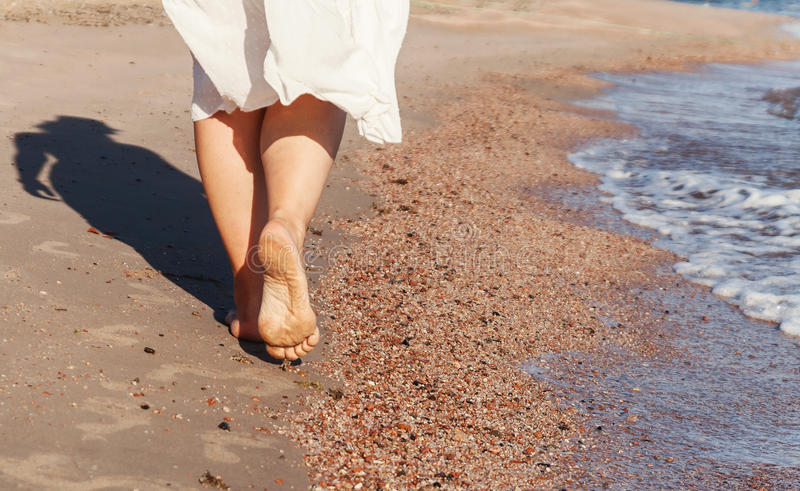 Curso das férias - close up do pé da mulher que anda na areia branca que relaxa no roupa de banho do pareo do encobrimento da pra foto de stock royalty free