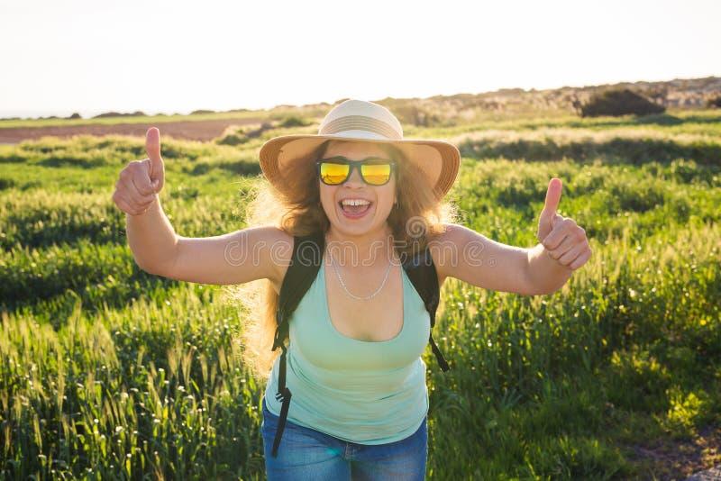 Curso das férias de verão e conceito da carona - mulher feliz bem sucedida que faz os polegares que aprovam acima o gesto no verã fotografia de stock
