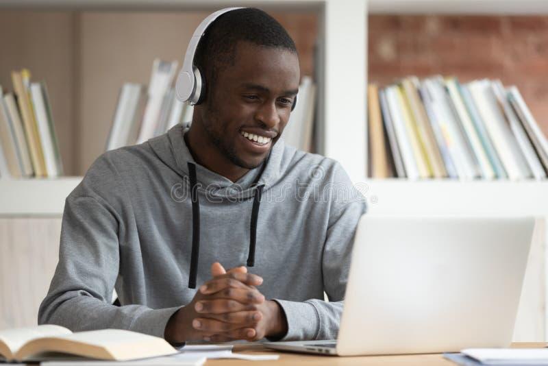 Curso de aprendizaje en línea masculino negro sonriente del reloj en el ordenador portátil fotografía de archivo libre de regalías