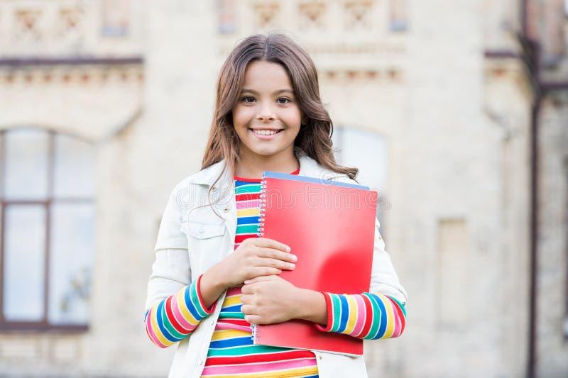 Curso de elección. Educación moderna. Estudiante de escuela de niñas sonrientes sostiene libros de texto para estudiar. Educaci fotografía de archivo