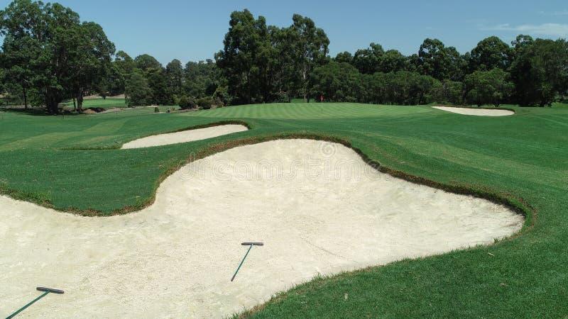 Curso de golfe verde com bandeira vermelha ao lado de bunker de areia e riscos com raios cercados por árvores contra céu azul imagens de stock