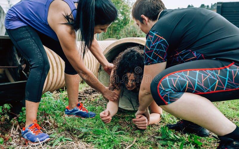 Curso de obstáculo dos participantes que atravessa uma tubulação imagens de stock